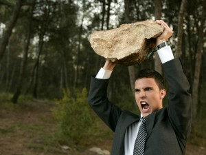 Young Man In Suit Holding Rock