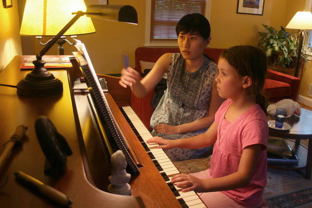 Girl with piano tutor