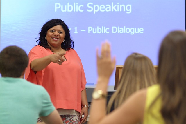 Woman in pink shirt teaching a Public Speaking class