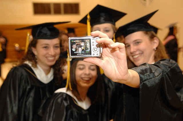 Graduates wearing black cap and gowns taking a selfie