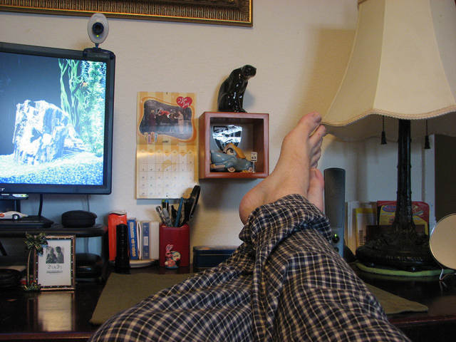 feet on a desk with tv computer webcam home office study working from home pajama pants