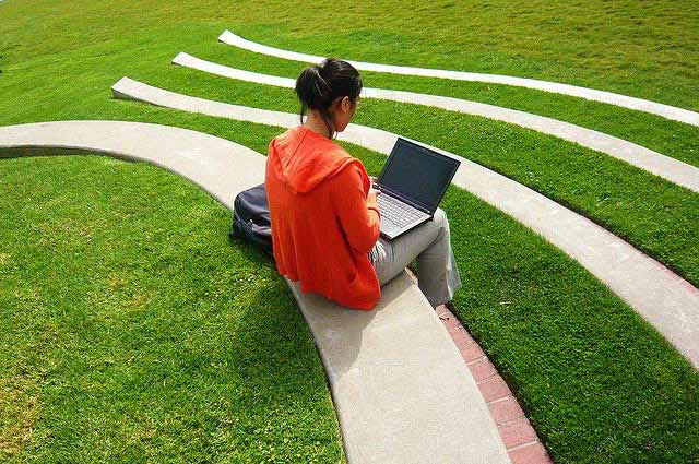 A girl studying outside on her laptop