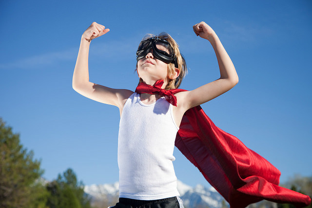 Young male confident in red cape superhero