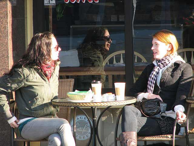 Two women having a conversation exchange over coffee