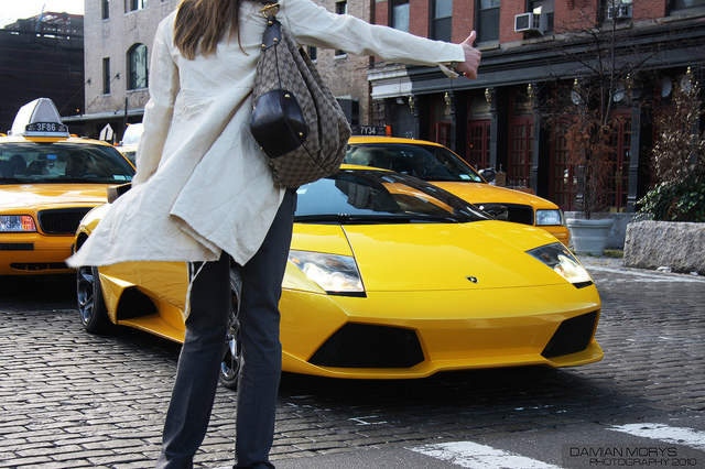 Woman Hailing Taxi Cab in City USA
