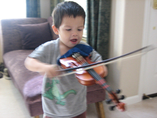 Young boy playing violin happily