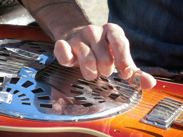 Man playing lap steel guitar horizontal slide guitarist