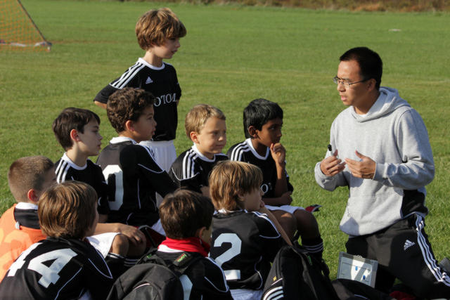 Man coaching young boys in Soccer